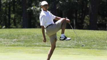 President Barack Obama reacts as he misses a shot while golfing.