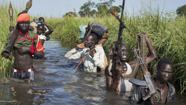 Rebel soldiers patrol and protect civilians from the Nuer ethnic group, as they walk through floods to reach a makeshift camp for the displaced in South Sudan last year.
