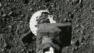 "The sampling arm of the OSIRIS-REx spacecraft during a rehearsal for an approach to the ""Nightingale"" sample site on the surface of the asteroid Bennu."