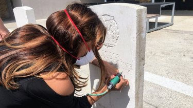 Latika Bourke attempts etching a Commonwealth War Grave headstone at the Commonwealth War Graves Experience centre in Arras, France