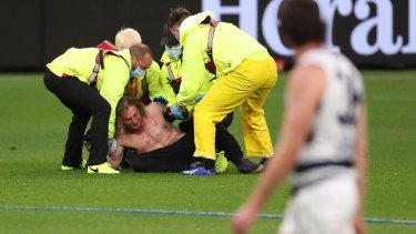 Optus Stadium security subdue the pitch invader, who faces a $50,000 fine.