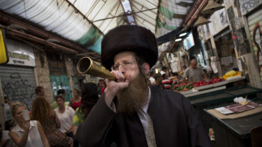 An Ultra-orthodox Jewish man blows a trumpet to announce the starting of the Sabbath, Judaism's biblically mandated day of rest, at the Mahane Yehuda market in Jerusalem.