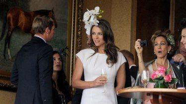 Sarah Jessica Parker takes a picture of Liz Hurley with Shane Warne in the chairman's private box during Oaks Day at Flemington.