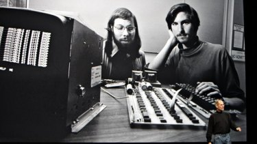 Steve Jobs talks in front of a picture of himself and Apple co-founder Steve Wozniak from 1977.