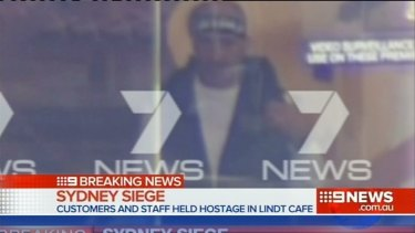Man Haron Monis is seen through the window of the Lindt cafe.