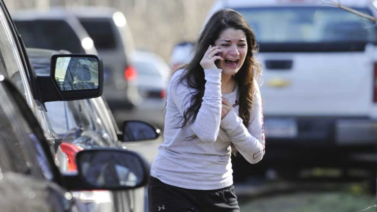 A woman waits to hear about her sister, a teacher, following a shooting at the Sandy Hook Elementary School in 2012.