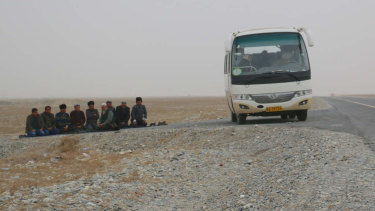 Uighur men stop their bus on the roadside to pray, on a highway leading into Hotan in Xinjiang.
