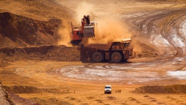 A haul truck is loaded by a digger with material in the pit at one of Rio Tinto's Pilbara iron ore mines.