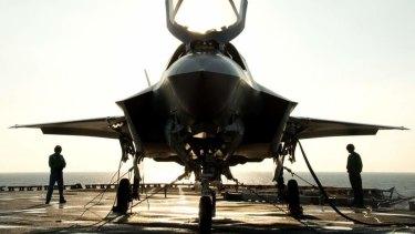 The flight deck crew secures an F-35B Lighting II aircraft aboard the amphibious assault ship USS Wasp.