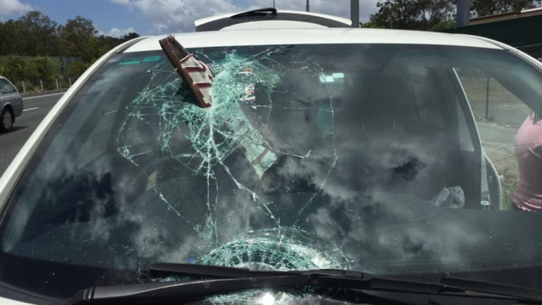 A woman has escaped without injury after a plate has smashed through the windscreen of her car in Queensland.