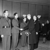 King Haakon VII of Norway at the premiere of the film Operation Swallow: The Battle for Heavy Water at Klingenberg kino. From left: Joachim Ronneberg, Jens Anton Poulsson shaking hands with the king, Kasper Idland.