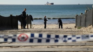 Police officers conduct an investigation on Stockton Beach.