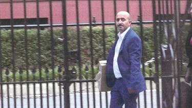 Property developer Jo Alha carrying a cardboard box of a model to a meeting with Daryl Maguire as seen in a photo submitted to the ICAC.