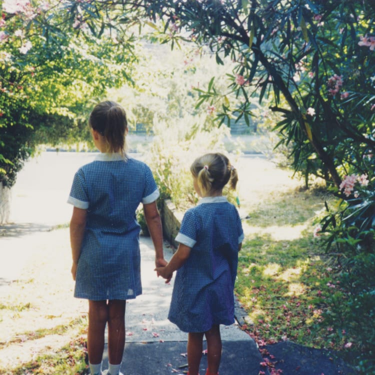 A five-year-old Anna (at right) heading down the driveway for her first day of school, led by her sister, Katie.