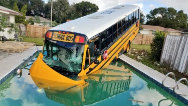 This photo released by the Orange County Sheriff's Office shows a Florida school bus that ploughed through a fence and into a backyard pool after a collision, but no one on board was hurt.