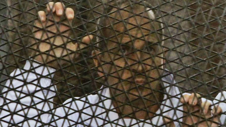 Peter Greste inside a defendants' cage in a courtroom during his trial.
