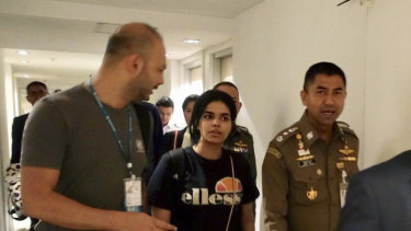 Chief of Immigration Police, Major General Surachate Hakparn (right) walks with Rahaf Mohammed al-Qunun as she leaves Suvarnabhumi Airport in Bangkok on Monday.