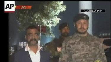 Wing Commander Abhinandan Varthaman, left, walks to cross the border into India, in Wagah, Pakistan, on Friday.