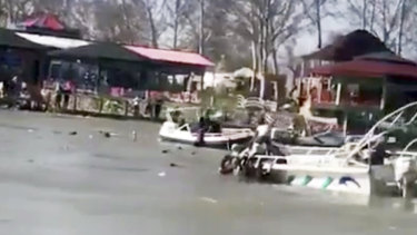An image taken from a witness's video shows boats trying to rescue people in the Tigris River after a overloaded ferry sank.