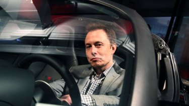Elon Musk, behind the wheel of a Tesla.