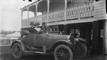 Three people in a single seat Ford car in front of a Queenslander style house with verandah taken by Queensland photographer Harriett Pettifore Brims.