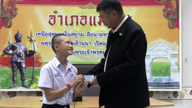 "Mongkol ""Mark"" Boonpiam, 14, left, receives an identity card denoting Thai citizenship from Mae Sai Sheriff Somsak Kunkam during a ceremony in Mae Sai on Wednesday."