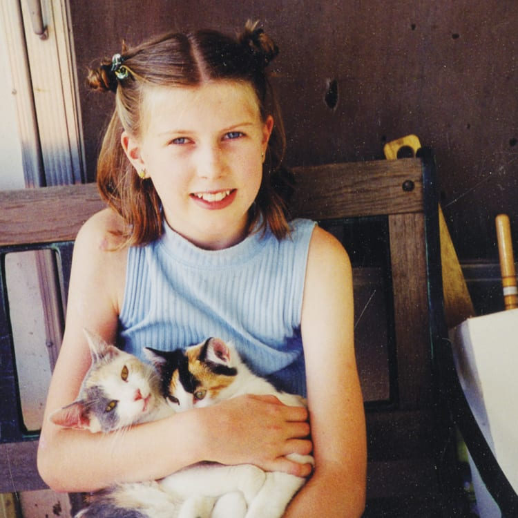 Anna, aged 11, with some kittens on a visit to the Iowa farm where her mother grew up.
