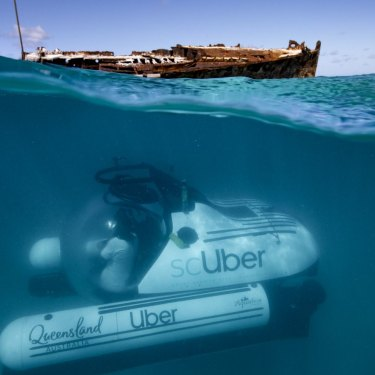 The ride-share submarine scUber, seen submerging near the shipwreck of HMAS Protector in the Great Barrier Reef.