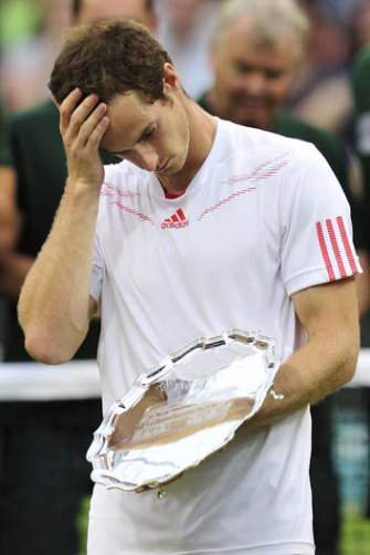 Britain's Andy Murray stands with his runners-up trophy after his 2012 Wimbledon men's singles final defeat to Federer.