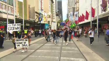 Protestors took issue with health restrictions and walked along Bourke Street Mall on Saturday.