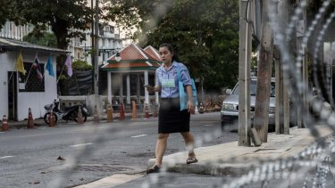 A Thai woman walks in front of the Crown Property Bureau in Bangkok, Thailand.