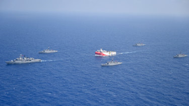 Turkey's research vessel, Oruc Reis, in red and white, is surrounded by Turkish navy vessels in the Mediterranean.