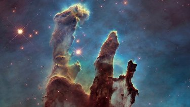 Pillars of Creation in the Eagle Nebula, captured by the Hubble telescope, with hydrogen shown as green. Sulphur is red and oxygen is blue.