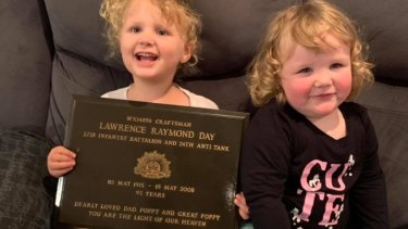 The great grand daughters, Emma and Aaliyah, of war veteran Lawrence Raymond Day holding his returned gravestone plaque.