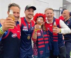 HaydenBurbank (left) inside the AFL rooms after Melbourne's win at the grand final.