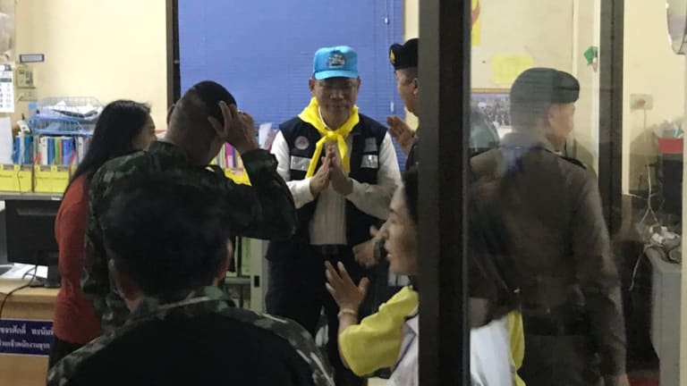 Rescue mission chief Narongsak Osottanakorn puts his hands together in the common Thai gesture of greeting and thanks.