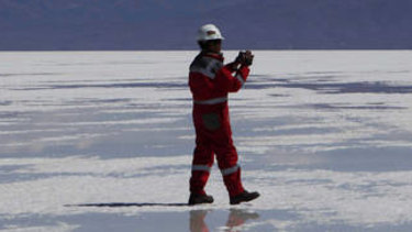 Rich in lithium: A worker walks on salt at a semi-industrial plant to produce potassium chloride, used to manufacture batteries based on lithium, at the Uyuni salt desert, outskirts of Llipi, Bolivia.