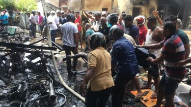 Witnesses go through the wreckage of the Zion Church in Batticaloa, Sri Lanka.