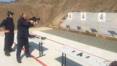 Police Minister David Elliott with a submachine gun at the opening of the Corrective Services NSW firing range in 2018.