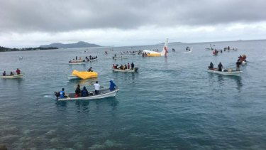 A number of locals in boats ferried passengers from the plane.