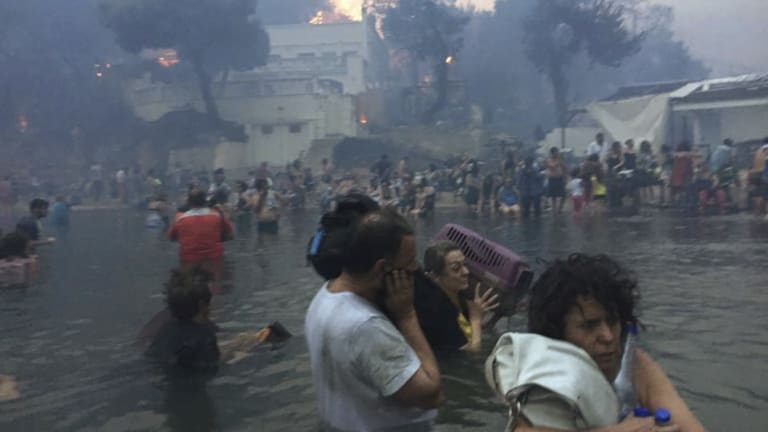 """Dozens shelter in the sea off the """"Silver Coast"""" beach in Mati, Greece as fire rips through the resort town on July 23."""