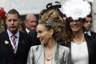 Flanked by security guards, actress Sarah Jessica Parker arrives for Ladies Day at Flemington in 2011.