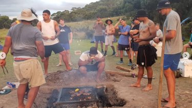 The Brumbies sit around the fire on their pre-season camp.