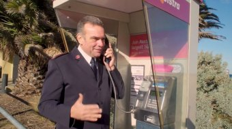 It's for you: The Salvation Army's Major Brendan Nottle at a St Kilda payphone.