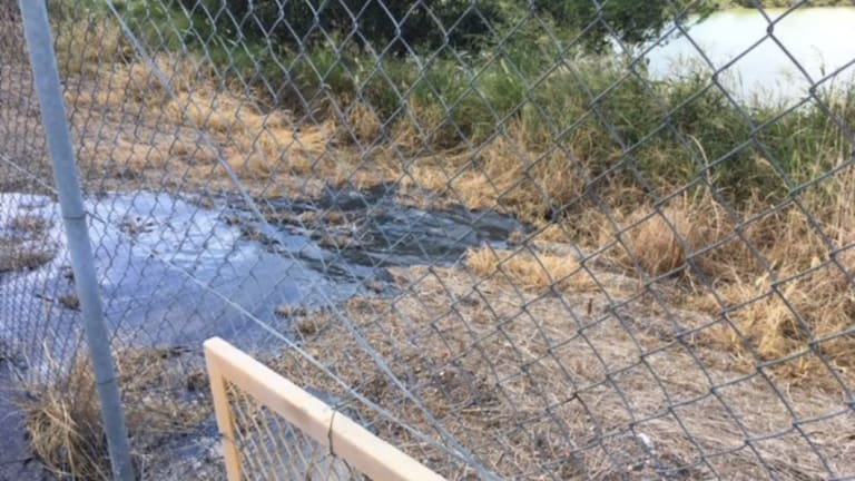Liquid leaking from an explosives storage facility beside the site of a proposed super dump at Ipswich on April 1.
