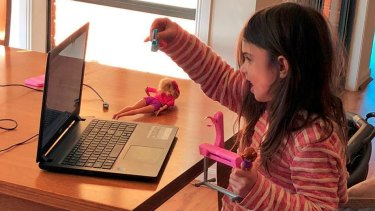Sadie, 5, shows her dolls to her educator Phoebe Wong over Zoom.