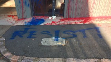 """""""Resist!"""" has been written in blue paint across the footpath in front of the LNP headquarters."""