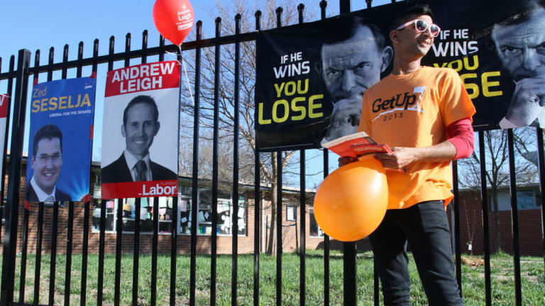 A GetUp! supporter hands out how-to-vote cards in the ACT during the 2013 election.