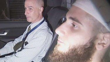 Agim Kruezi (right) after his 2014 arrest.
