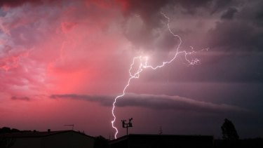 Lightning strikes with the backdrop of a red sky in the Ipswich suburb of Karalee on Wednesday night.